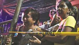 A relative of a victim cries behind the police line at the site of a drug-related shooting by uniden