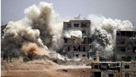 Smoke rises around buildings following a reported air strike on a rebel-held area in the southern Sy