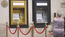 A woman uses a smart phone to take a photograph of a gold coloured automated teller machine installe