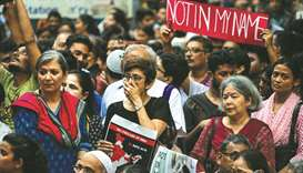 Protesters hold placards as they gather for a 'Not in my name' silent protest at Jantar Mantar in Ne