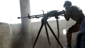 A member of the Kurdish People's Protection Units (YPG) fires a machine gun in the Syrian city of Ra