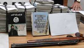 Indonesian police show scores of notebooks inscribed with Islamic State propaganda seized during a r
