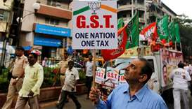 A supporter holds a placard  to support implementation of GST in Mumbai