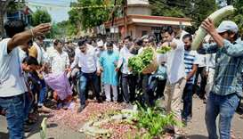 People throwing vegetables on a road during their nation-wide strike and agitation over various dema