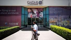 A man walks past Qatar Airways office in Manama, Bahrain.