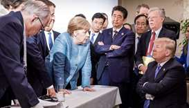 US President Donald Trump (R) talking with German Chancellor Angela Merkel (C) and surrounded by oth
