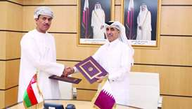 Dr Ibrahim bin Saleh al-Nuaimi and Najeeb bin Yahya Al Balushi exchanging the documents after signin