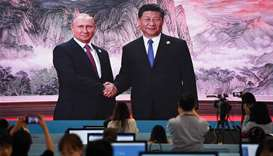 A large video screen shows Chinese President Xi Jinping shaking hands with Russia's President Vladim