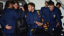 Neymar and his team mates disembark from a plane.