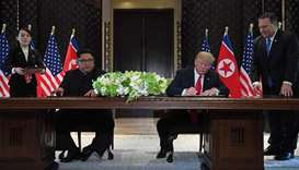 US President Donald Trump (2nd R) and North Korea's leader Kim Jong Un (2nd L) sign documents
