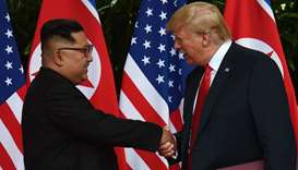 North Korea's leader Kim Jong Un (L) shakes hands with US President Donald Trump (R)