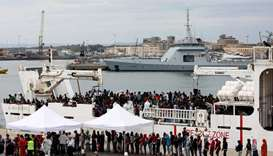 "Migrants disembark Italian coast guard vessel ""Diciotti"" as they arrive at the port of Catania, Ital"