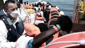 Rescued migrants and MSF personnel onboard an Italian coastguard ship following their transfer from