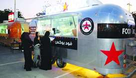 Customers place their orders at one of the food trucks outside the Khalifa International Stadium