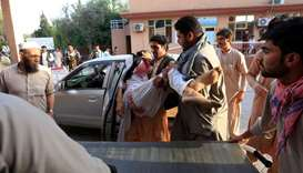 Men carry an injured man in a hospital after a car bomb, Jalalabad city