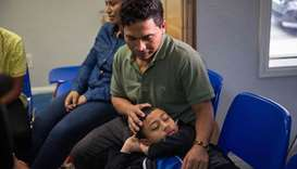 An immigrant from El Salvador and his 10-year-old son pass the time after being released from detent