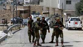 Israeli soldiers stand at the scene of alleged car ramming attack, in Hebron in the occupied West Ba