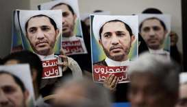 Bahraini men hold placards bearing the portrait of Sheikh Ali Salman in the village of Zinj on the o