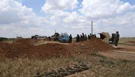 Syrian government soldiers inspect a vehicle arriving in a convoy carrying displaced people