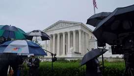 Television reporters wait prior to the US Supreme Court's decision to impose limits on the ability o
