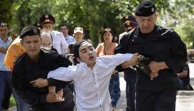 Police officers detain an opposition supporter attempting to stage a protest rally in Almaty