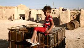 A Syrian child from the northern city of Manbij sits outside mud-brick dwellings at Al-Qadi camp