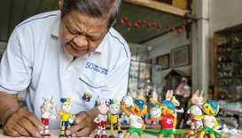 Nguyen Thanh Tam displaying various Football World Cup mascots including Fuleco (front R), the 2014