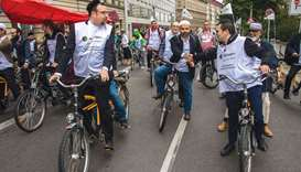 Jews and Muslims, one person of each faith sharing a tandem bicycle, are seen at the start of the 'M