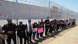 Protesters link arms after tying children's shoes and keys on the fence outside the Otay Mesa Detent
