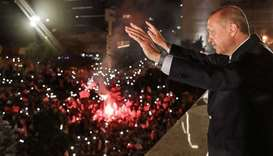 Turkish President Tayyip Erdogan waving to supporters gathered above a balcony at the headquarters o