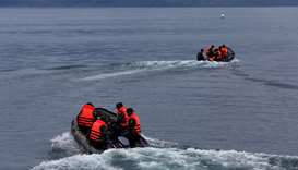 Rescue team members use rubber boats during a search operation for missing passengers after a ferry