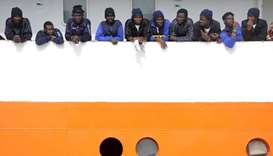 Migrants wait to disembark from Aquarius in the Sicilian harbour of Catania, Italy