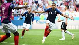 France's forward Kylian Mbappe (R) celebrates after scoring their third goal