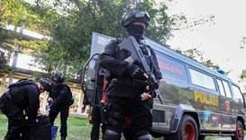 Indonesian anti-terrorism policeman holds a rifle as others seized crude bombs at Riau University bu