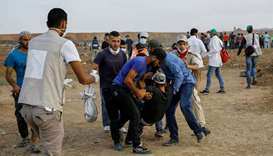 Palestinian protesters carry away a wounded comrade during a demonstration along the border with Isr
