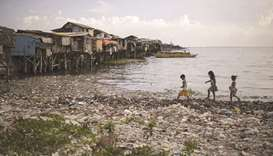 A recent photo shows children walking along a garbage-filled bay in Manila.