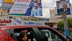 A poster erected on a main street in the West Bank town of Hebron next to a portrait of the Palestin