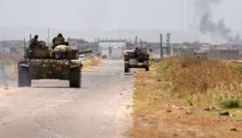 A tank belonging to the Syrian regime forces drives on a road leading to the town of Jalamah in Syri