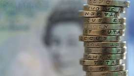 British one pound coins stand stacked near the printed face of Queen Elizabeth II on a five pound no