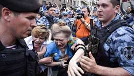 Russian police officers detain protesters during a march to protest against the alleged impunity of