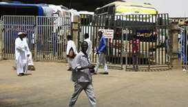 People walk past at the main bus station in Khartoum, linking the Sudanese capital with various part