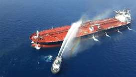 An Iranian navy boat tries to stop the fire of an oil tanker after it was attacked in the Gulf of Om