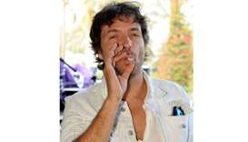 Philippe Zdar smokes backstage during day three of the Coachella Valley Music & Arts Festival 2010