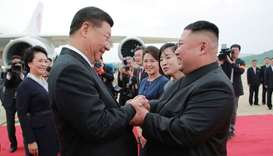 North Korean leader Kim Jong Un (R) shaking hands with Chinese President Xi Jinping upon his arrival