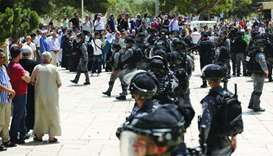 Israeli security forces stand guard in front of a group of Palestinians at the Al Aqsa Mosque compou