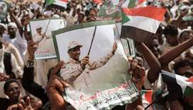 Supporters hold portraits of Mohamed Hamdan Dagalo (R) and commander of the Rapid Support Forces (RS