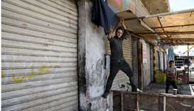 A shop owner puts a black flag in front of his closed shop during a strike called by local activists