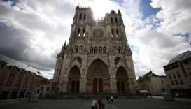 People stand in front of the Cathedral of Notre-Dame d'Amiens in Amiens, France