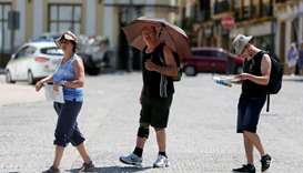 A tourist uses an umbrella to protect himself from the sun, as a heatwave hits Spain, in Ronda, sout