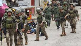 Soldiers walk past the body of a man slumped beside a tricycle following an armed attack in front of